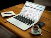 Mock-up image of Frontiers in Immunology landing page displayed on a Macbook, placed on a wooden desk, with a notebook, cup of coffee and iPhone next to it