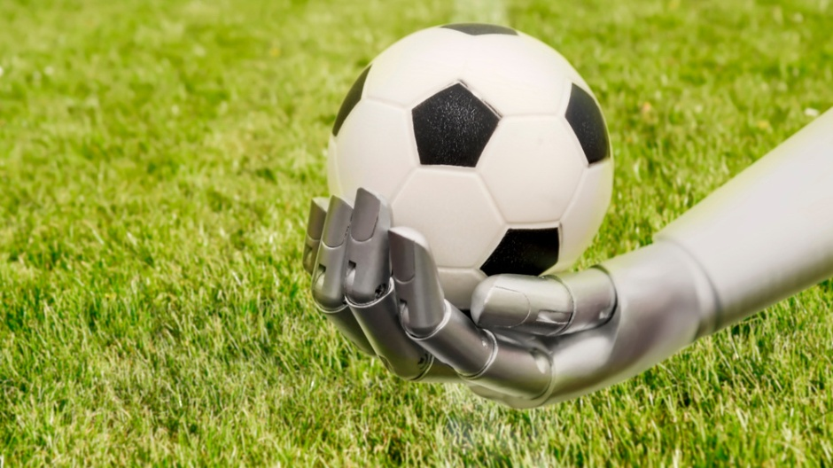 Image of robot arm holding a football (soccer ball). Football-playing robots trained to walk using real infant walking paths scored more goals and won more games than robots trained to walk in straight lines, circles or squares: Frontiers in Neurorobotics