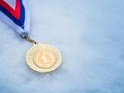 Picture of gold medal in snow. The training secrets of the world's most successful cross-country skier, Marit Bjørgen, could help women wanting to return to sports after pregnancy: Frontiers in Physiology