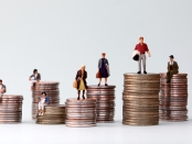 Miniature people standing on piles of different heights of coins. Income and economic inequality concept.