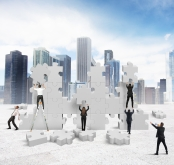 Image of individuals with life-sized jigsaw blocks against a city skyline backdrop