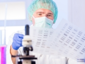 Male scientist looking at genome codes in a lab amongst scientific apparatus