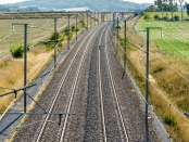 View from above of a french high-speed railway track with overhead line equipment, made of posts, catenaries, wires and power lines to supply bullet trains
