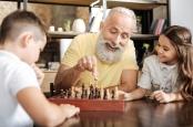 Elderly man plays chess with his grandchildren