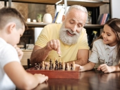Elderly man plays chess with his grandchildren