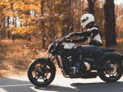 A young guy in a helmet is riding on a forest road on an electric motorcycle. He sits confidently in the saddle. There are green trees around him