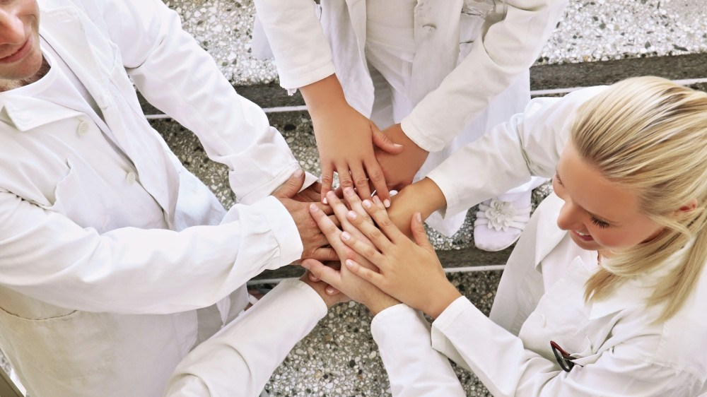 Group of young scientists and doctors holding hands together. Medicine, support, science, research, pharmacy Technology, recycling, research, chemistry, support and teamwork concept.