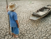 Global warming, Child with boat on cracked earth after the climate change