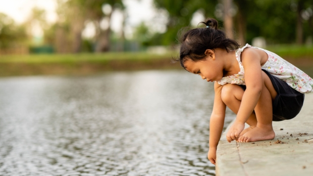 Cute little girl is sitting is playing along the pond