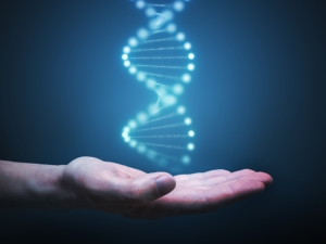 DNA and genetics research concept. Hand is holding glowing DNA molecule in hand