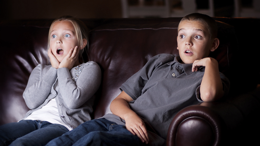 "Image of shocked children watching television. New research shows that ""justified"" and ""unjustified"" violence in movies produces different brain responses, finds study in Frontiers in Behavioral Neuroscience."
