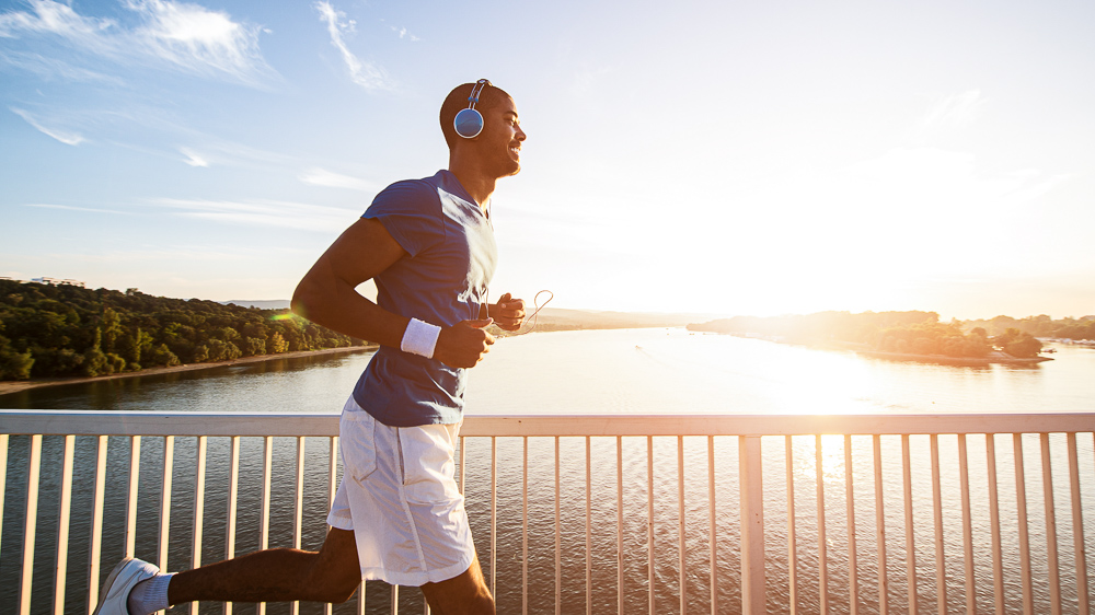 Image of man running across bridge. High-tempo music may increase the benefits of exercise and reduce perceived effort: Frontiers in Psychology