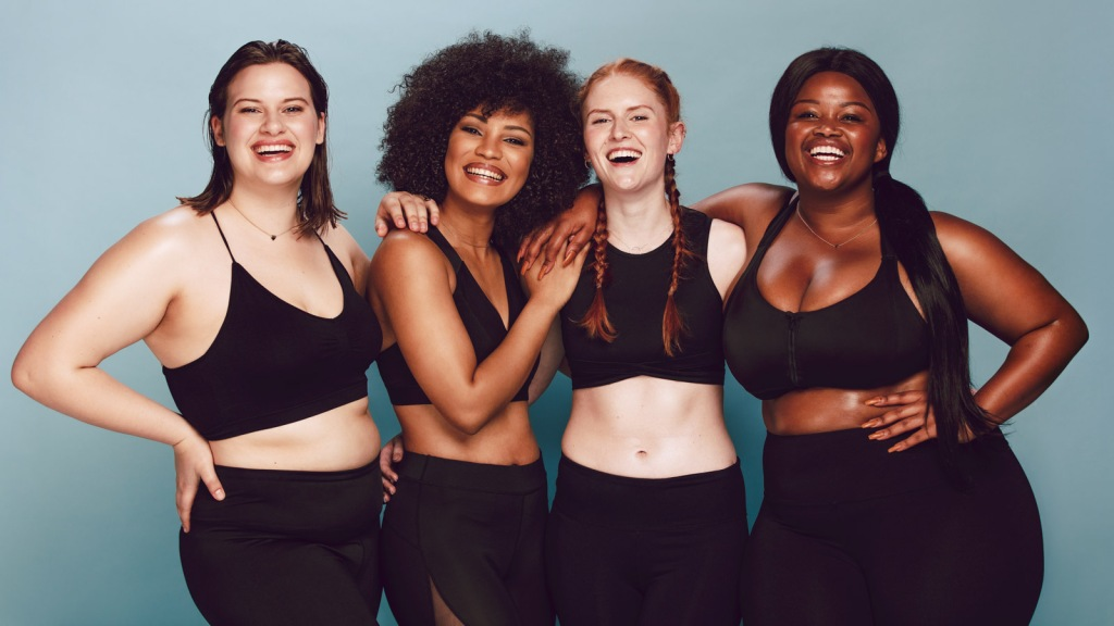Picture of a group of women with a range of body shapes smiling. People rate their own bodies as more attractive when viewed from a third-person perspective: Frontiers in Robotics and AI.