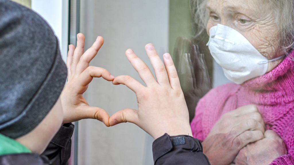 Image of child holding up hands in heartshape to grandmother through a window. Patients can be at risk of cardiovascular impairment and should be given proven treatments to aid survival and recovery: Frontiers in Cardiovascular Medicine