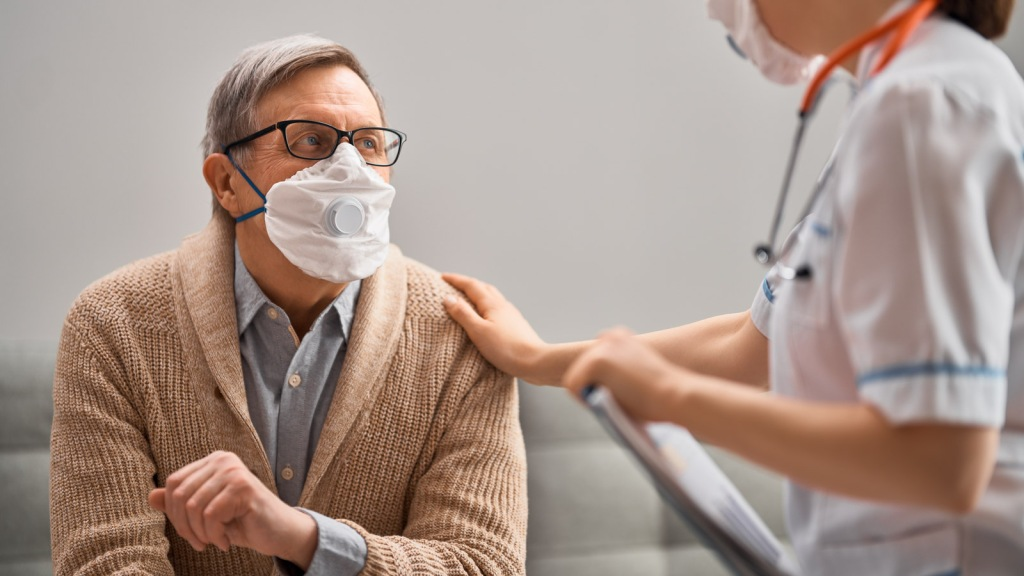 Image of elderly man in mask being comforted by a doctor. Study of gender differences in COVID-19 finds that men have more severe disease and are over twice as likely to die: Frontiers in Public Health