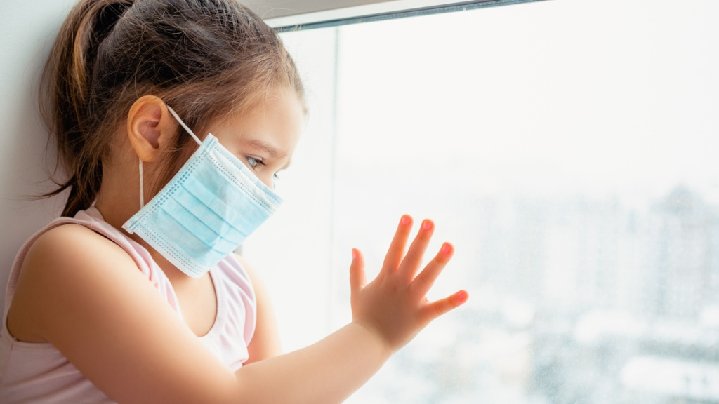 Image of child in face mask looking outside a window. Gastrointestinal symptoms, coupled with a fever or history of exposure to COVID-19, could indicate coronavirus infection in children: Frontiers in Pediatrics