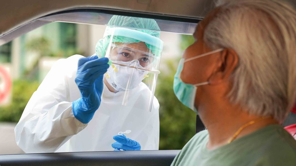 Image of woman in PPE administering a nasal swab test to patient in a car. COVID-19 Ag Respi-Strip test can identify an infected person in 15 minutes at point-of-care sites that lack facilities or time for sophisticated testing: Frontiers in Medicine.