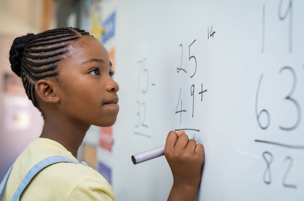 Image of a girl in school writing a math calculation on a whiteboard There are gender differences in the interests in mathematics schoolwork, finds study in Frontiers in Psychology