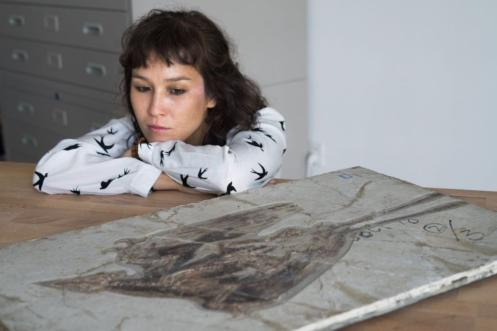Jingmai O'Connor crossing her arms and leaning on a table while looking at fossilized remains of a bird.