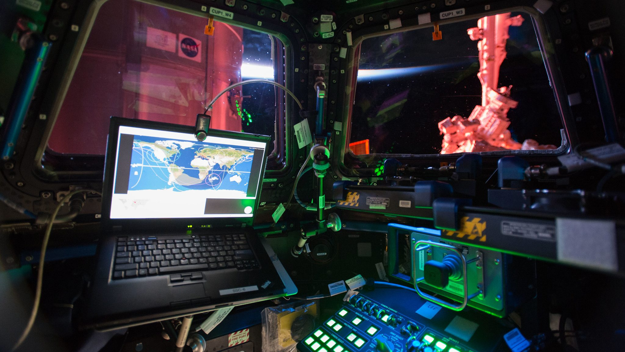 Interior view from the International Space Station cupola bathed in green, blue and red lights.