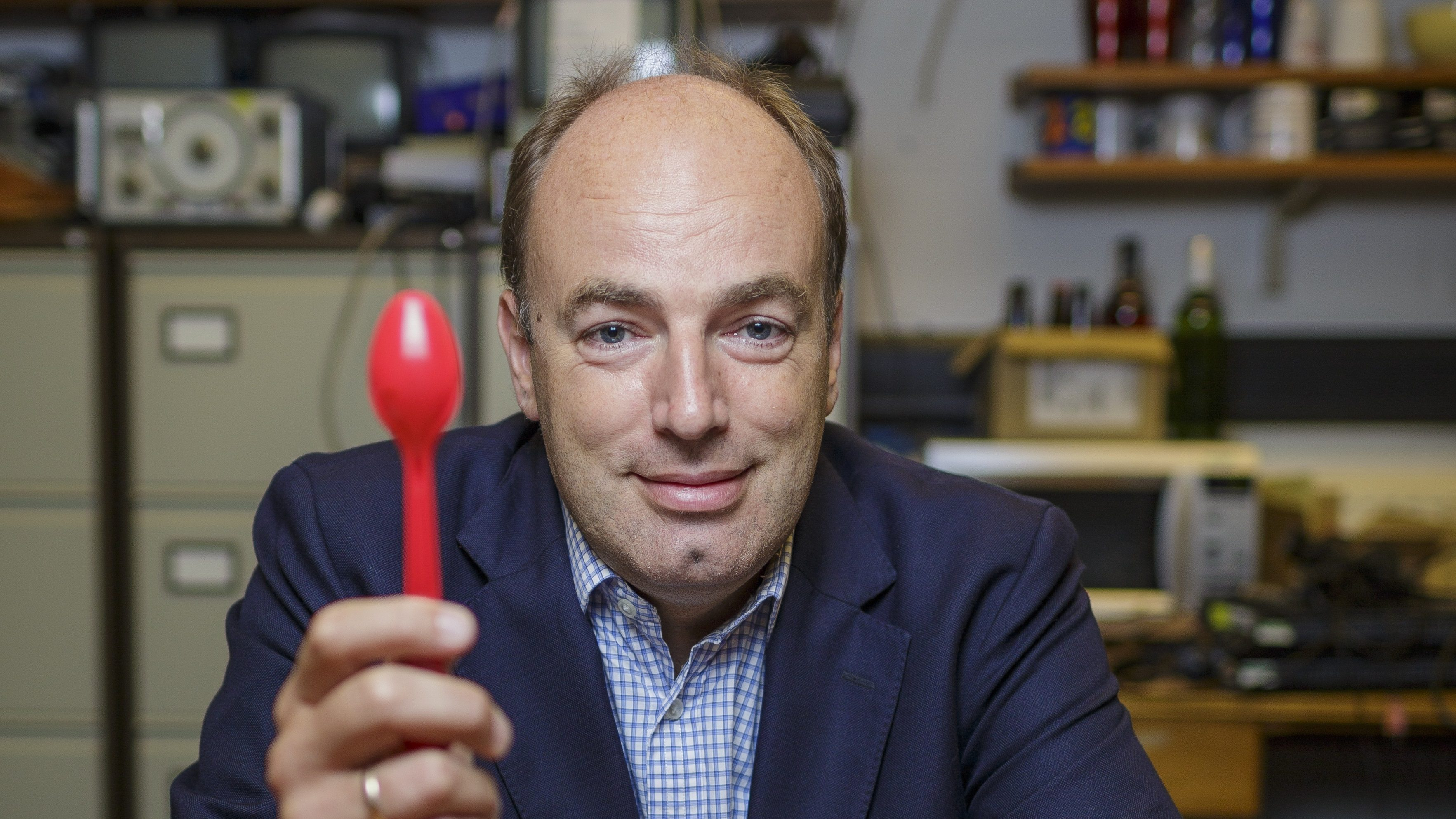 Prof Charles Spence in a blue blazer and checkered shirt smiling and holding up a red spoon.