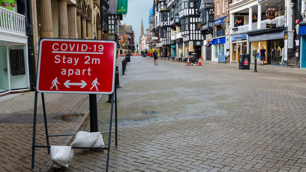 """Red street sign that says """"Covid-19: stay 2 meters apart"""" on an empty high street."""