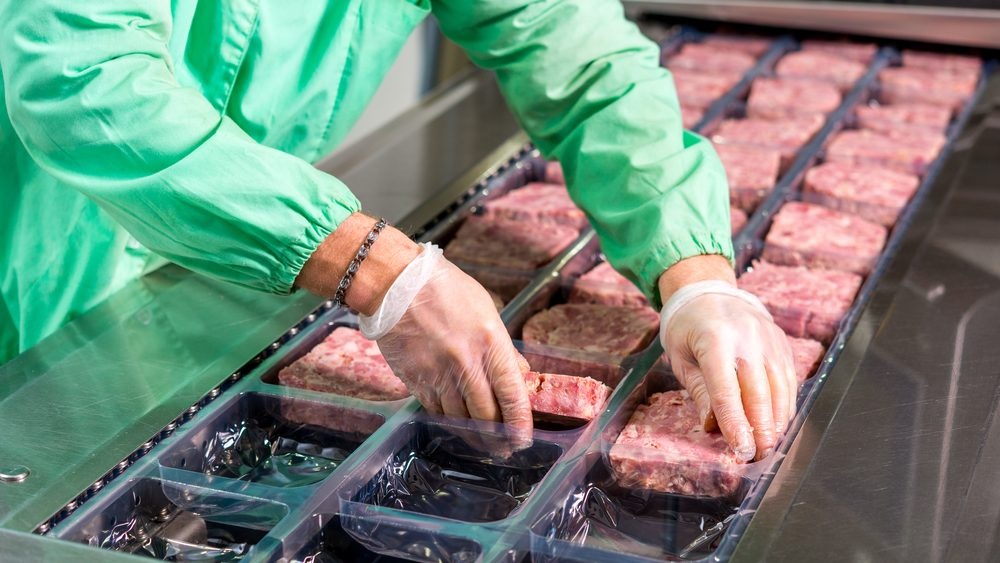 Person wearing green overalls and surgical gloves placing meat into packaging.