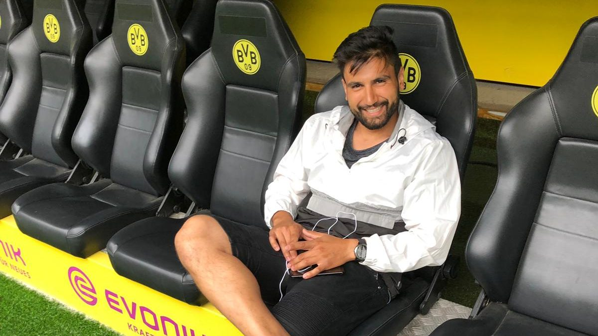 Dr Nima Dehghansai smiling and sitting in a black leather chair at a football stadium against a yellow background.