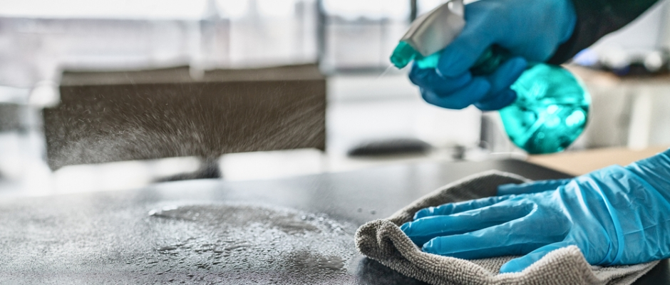 Person wearing blue cleaning gloves spraying a surface with antibacterial spray.