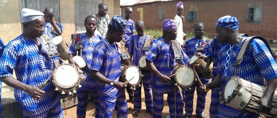 Dundun drummers in bright blue clothing playing the drums in a rural setting.